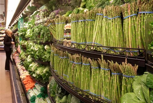 In this March 1, 2011 file photo, a customer looks at fresh vegetables at a Kroger Co. supermarket in Cincinnati. Consumers paid more for food, gas and rent last month, but outside those categories inflation remained tame.(AP Photo/Al Behrman, file)