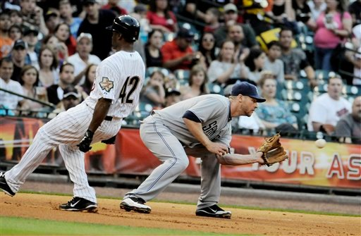 Houston Astros' Michael Bourn, left, is easily safe at third base ahead of the catch by San Diego Padres third baseman Chase Headley, right, during the first inning of a baseball game Friday, April 15, 2011, in Houston.