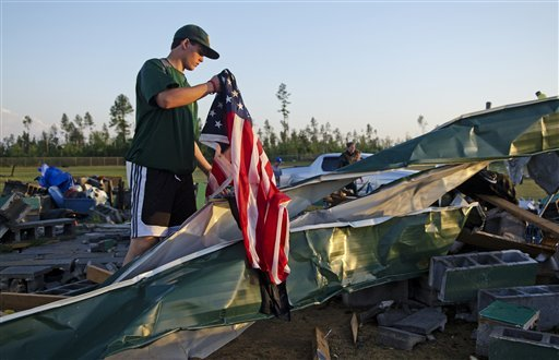 Patrick Woods, a freshman at Pine Forest High School in Fayetteville, N.C. picks up a flag on the remains of structures on the softball field at Pine Forest High School Saturday, April 16, 2011 in Fayetteville, N.C.  (AP Photo/The Fayetteville Observer)