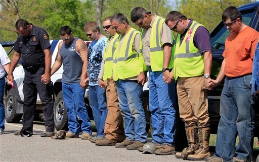 Rescue workers pray together on Thursday, April 14, 2011, in Parsons, Tenn. Searchers are looking for 20-year-old nursing student Holly Bobo, who was last seen Wednesday being dragged from her house by a man wearing camouflage.