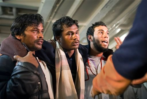 A weak evacuee, center, is helped by another, left, and an aid worker, right, as nearly 1,200 migrant workers who were evacuated from Misrata by boat, many suffering from dehydration and needing medical attention, arrived at the port in Benghazi, Libya.