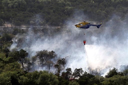 A Travis Co. Star Flight helicopter drops water on a wildfire that destroyed homes in southwest Austin, Texas on Sunday, April 17, 2011.(AP Photo/Jack Plunkett)