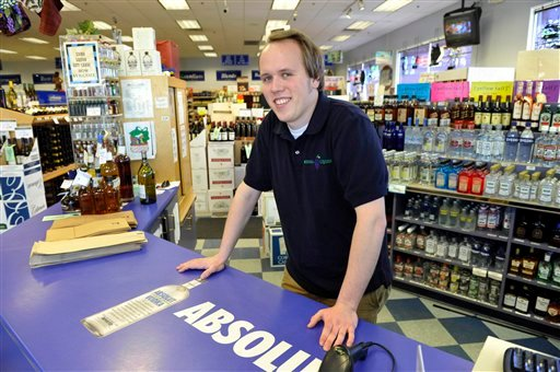 In this photo made April 6, 2011, Mark McNally is shown at his part-time job at a liquor store in Edina, Minn. McNally, 23, earned a history degree from the University of Minnesota. (AP Photo/Jim Mone)