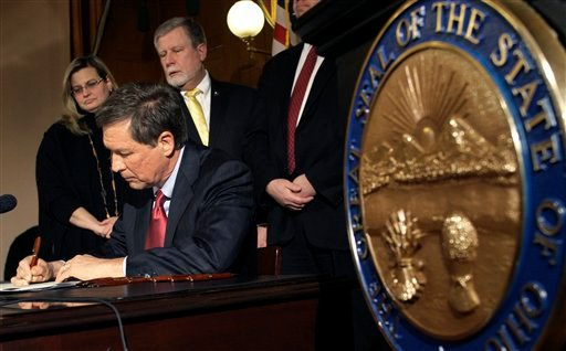 March 31, 2011, file photo: Ohio Gov. John Kasich, sitting, signs Senate Bill 5 into law as members of the Ohio Senate and Ohio House of Representatives watch in Columbus, Ohio. (AP Photo/Jay LaPrete)