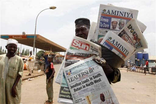 A man sells local newspapers with election headlines, indicating incumbent President Goodluck Jonathan leading, in Kaduna, Nigeria, Sunday, April 17, 2011.
