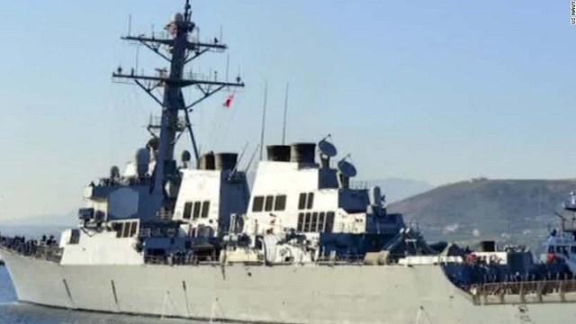 An American defense official says a U.S. Navy patrol boat fired warning shots near an Iranian naval ship.