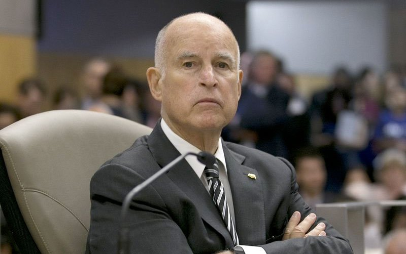 California Gov. Jerry Brown listens as members of the Senate Environmental Quality Committee discuss a pair of climate change bills he supports, in Sacramento, Calif.
