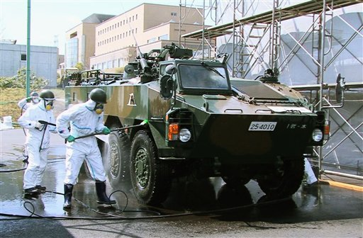 In this April 12, 2011 photo released by the Japan Defense Agency via Kyodo News, Japanese soldiers wash an armored vehicle to remove potential radiation contamination at J-Village. (AP Photo/Japan Defense Agency via Kyodo News)