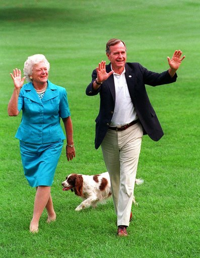 This Aug. 24, 1992 file photo shows President Bush, right, and first lady Barbara Bush walking with their dog Millie across the South Lawn as they return to the White House.