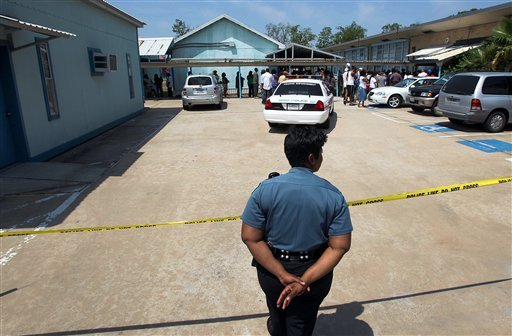 A Houston Independent School District police officer monitors an entrance after a shooting at Ross Elementary school Tuesday, April 19, 2011, in Houston.