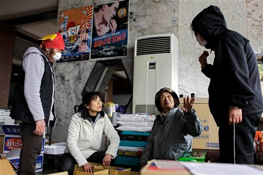 People sort out food in an evacuation center in an area devastated by the March 11 earthquake and tsunami in the port town of Kessenuma, Iwate Prefecture, Japan, Tuesday, April 19, 2011.