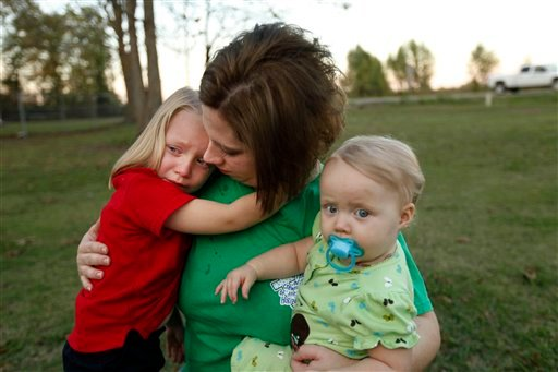 In this Nov. 11, 2010 photo, Courtney Kemp, widow of Roy Wyatt Kemp, 27, who died in the Deepwater Horizon oil rig explosion, holds her daughters. (AP Photo/Gerald Herbert, file)