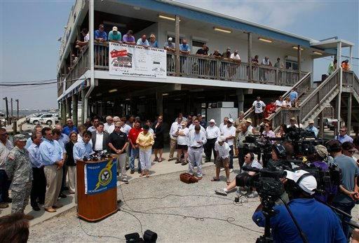 Louisiana Gov. Bobby Jindal, at podium, speaks at a news conference on the first anniversary of the Deepwater Horizon oil spill at a marina in Grand Isle, La., Wednesday, April 20, 2011.