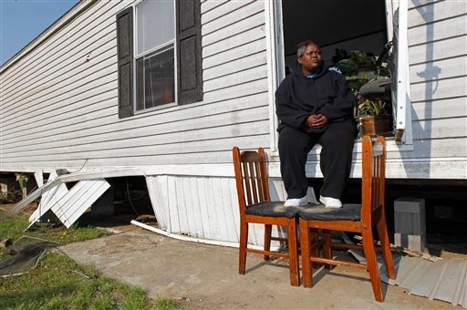 Terry Burgess sits in the doorway of her damaged home at a mobile home community in Dunn, N.C., Tuesday, April 19, 2011, after a tornado ripped through the area Saturday.