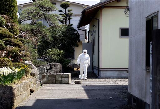 A man wearing a protective suite walks in the yard in the deserted town of Futaba, inside the 20-kilometer (12-mile) evacuation zone, in Fukushima Prefecture, Japan, April 21, 2011. (AP Photo/Sergey Ponomarev)