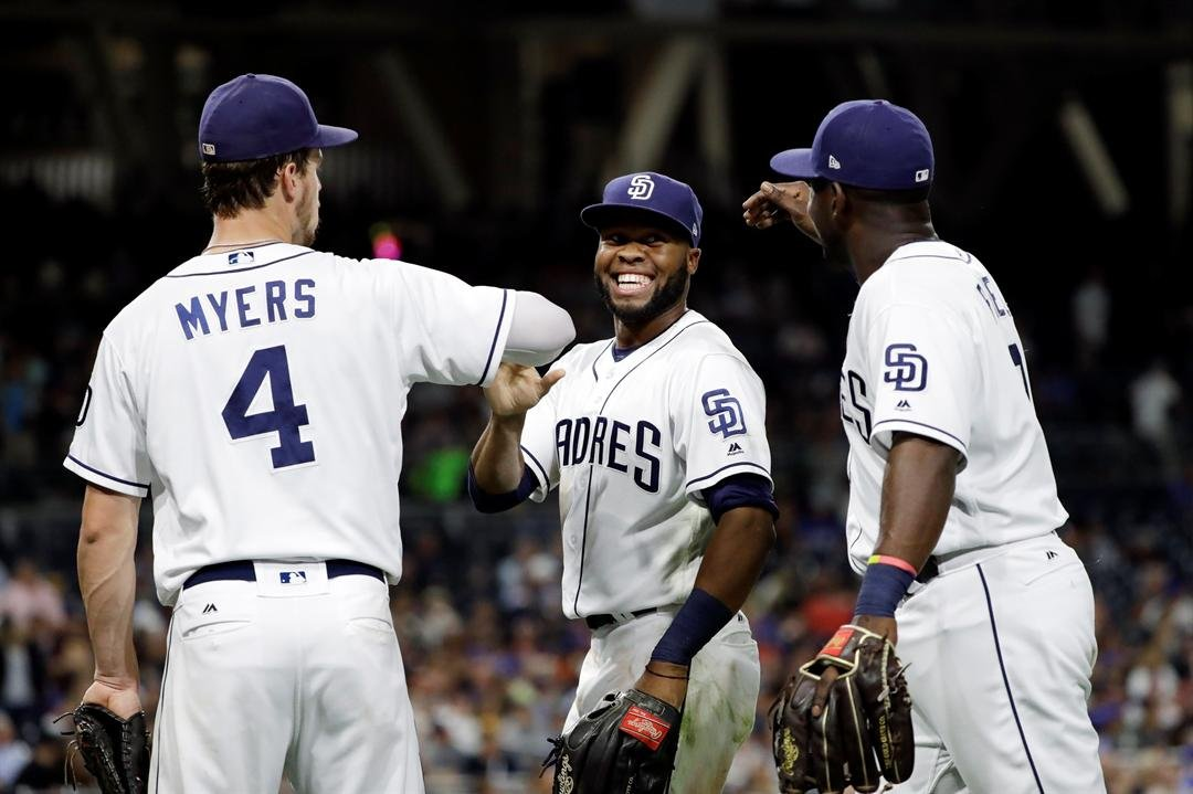San Diego Padres center fielder Manuel Margot, center, is greeted by first baseman Wil Myers, left, and left fielder Jose Pirela after making a catch for the out on New York Mets' Michael Conforto during the fifth inning of a baseball game Wednesday, July