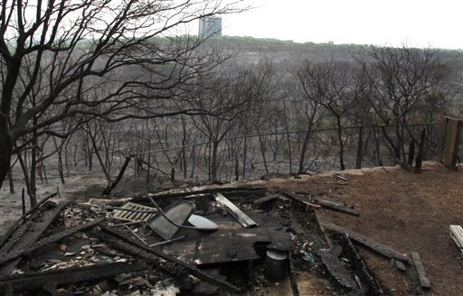 Debris and burned trees are shown on Monday, April 18, 2011, a day after a massive wildfire ravaged the Austin, Texas, wildfire. The fire damaged at least 21 homes.