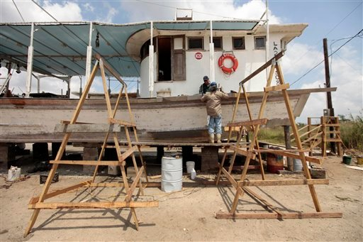 Norwood La.Cross and Donnie Tayamen work on a friends oyster boat as it sits in dry dock due to the ruined oyster beds, on the first anniversary of the Deepwater Horizon oil spill. (AP Photo/Gerald Herbert)
