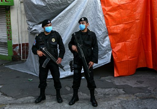 Mexico City police guard a refrigerated truck carrying bodies that were found in mass graves in northern Mexico, after it arrived in Mexico City, Thursday April 14, 2011.