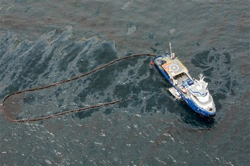 FILE - In this April 23, 2010 file photo, taken in the Gulf of Mexico more than 50 miles southeast of Venice on Louisiana's tip, a boat with an oil boom tries to contain oil spilled from the explosion and collapse of the Deepwater Horizon oil rig.