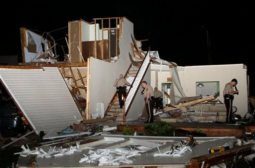 Officers from the St. Louis County police department inspect the remains of a home on Beaverton Drive in St. Louis Missouri after what residents believe was a tornado touched down earlier in the evening, Friday, April 22, 2011.