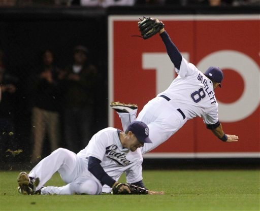 San Diego Padres shortstop Jason Bartlett trips over the sliding Ryan Ludwick after catching a bloop fly hit by Philadelphia Phillies' Wilson Valdez in the seventh inning of a baseball game Friday, April 22, 2011 in San Diego. (AP Photo/Lenny Ignelzi)