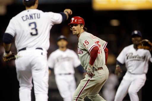 Philadelphia Phillies' Cole Hamels, center, is caught in a rundown in the second inning against the San Diego Padres in a baseball game on Friday, April 22, 2011, in San Diego. Hamels was eventually tagged out. (AP Photo/Lenny Ignelzi)