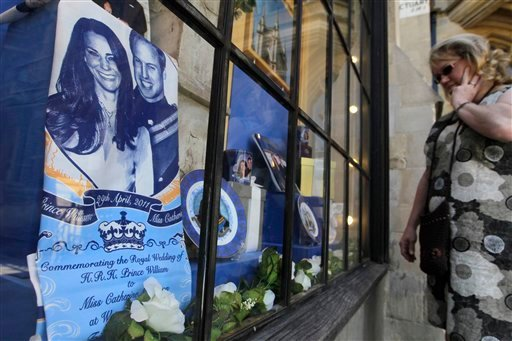 A woman looks into a Westminster Abbey's shop window displaying souvenirs of Prince William and Kate Middleton, London, Friday, April 22, 2011. Prince William and Kate Middleton are to marry at Westminster Abbey in London on April 29. (AP Photo/Sang Tan)