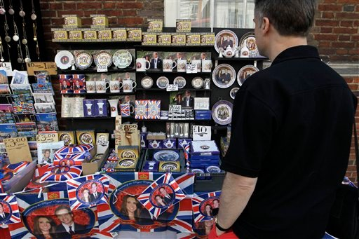 A man looks at souvenirs of Prince William and Kate Middleton on display at a street stall in London, Friday, April 22, 2011. Prince William and Kate Middleton are to marry at Westminster Abbey in London on April 29. (AP Photo/Sang Tan