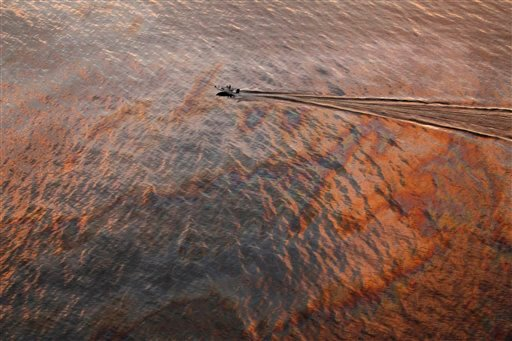 FILE - In this July 31, 2010 file photo, a boat motors through oil sheen from the Deepwater Horizon oil spill off East Grand Terre Island, where the Gulf of Mexico meets Barataria Bay, on the Louisiana coast, at sunset.