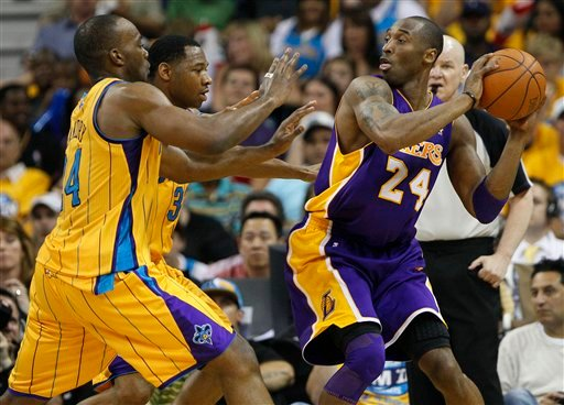 Los Angeles Lakers guard Kobe Bryant (24) keeps the ball away from New Orleans Hornets forward Carl Landry, far left, and guard Willie Green during the first half of Game 3 of a first-round NBA basketball playoff series in New Orleans, Friday.