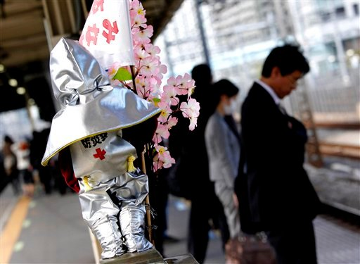 A statue of Manikin Piss decorated with cherry blossoms and disaster prevention gear stands in a station in Tokyo, Japan, Thursday, April 7, 2011. (AP Photo/Shuji Kajiyama)