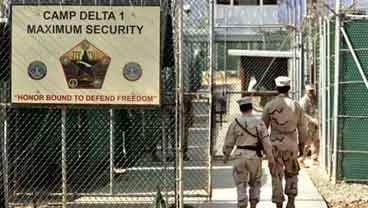 June 27, 2006 file photo: U.S. military guards walk within Camp Delta military-run prison, at the Guantanamo Bay U.S. Naval Base, Cuba. (AP Photo/Brennan Linsley, File)
