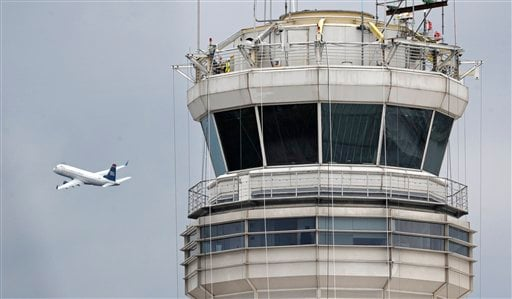 FILE - In this March 24, 2011 file photo, a passenger jet flies past the FAA control tower at Washington's Ronald Reagan National Airport.
