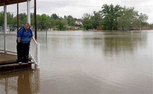 Erica Cross stands on a friend's porch surrounded by floodwater Tuesday, April 26, 2011, in Poplar Bluff, Mo. (AP Photo/Jeff Roberson)