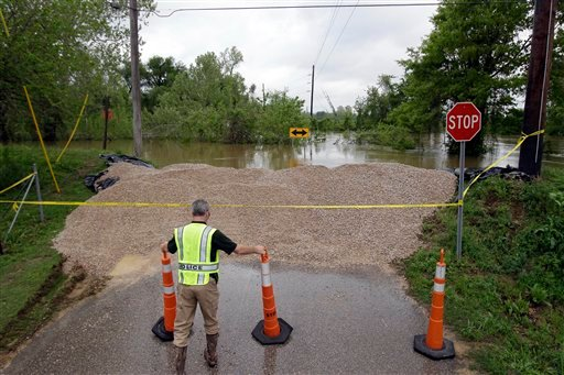 Detective Corey Mitchell with the Poplar Bluff Police Department adjusts traffic cones near a temporary levee holding back water from the Black River Tuesday, April 26, 2011, in Poplar Bluff, Mo.
