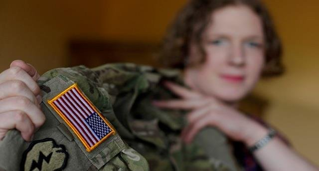 In this July 29, 2017 photo transgender U.S. army captain Jennifer Sims lifts her uniform during an interview.
