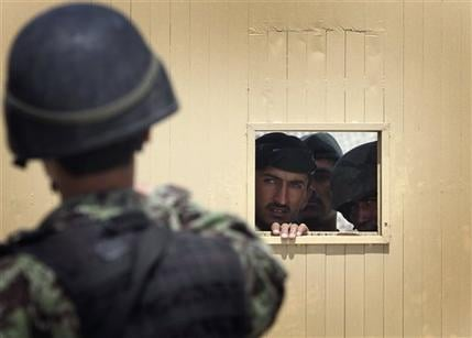 Afghan soldiers look out through the security hole of one of the gates at the airport after a firing incident in Kabul, Afghanistan on April 27, 2011. (AP Photo/Musadeq Sadeq)