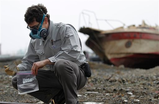 In this April 22, 2011 photo, EFA Laboratory manager Eric Eguina puts a sample material in a plastic bag while looking for materials possibly containing asbestos in an area devastated by the March 11 tsunami in northeastern Japan.