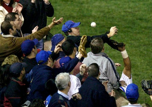 In this Oct 14, 2003 file photo, Steve Bartman catches a ball as Chicago Cubs left fielder Moises Alou's arm is seen reaching into the stands, at right, against the Florida Marlins.