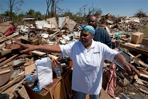 Elizabeth Williams points out where the tornado came from as she stands among the debris of her home in Tuscaloosa, Ala., Friday, April 29, 2011. Williams, two sons and a daughter survived the storm by hiding together in a closet.