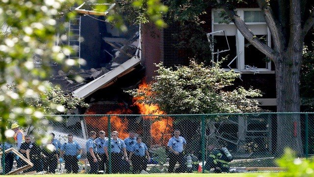 Emergency personnel move away as a gas fire continues to burn following an explosion at Minnehaha Academy Wednesday, Aug. 2, 2017, in Minneapolis.