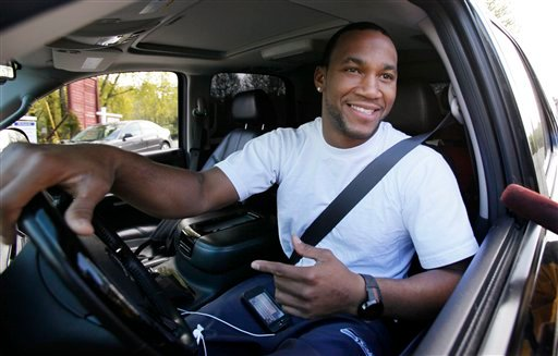 Seattle Seahawks defensive back Roy Lewis smiles as he stops to chat with media members while driving into the team's headquarters Friday, April 29, 2011, in Renton, Wash. (AP Photo/Elaine Thompson)