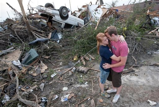 Daniel Mulder hugs his wife Rachael near their destroyed apartment in Tuscaloosa, Ala., Saturday, April 30, 2011. Mulder and his wife survived the Wednesday tornado hiding in a tub before coming the assistance of their neighbors. (AP Photo/Dave Martin)