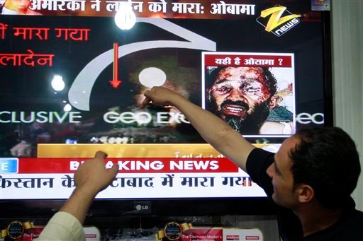 Afghan men point at a television screen as the killing of Al-Qaida leader Osama bin Laden is announced at TV shop in Kabul, Afghanistan Monday, May 2, 2011.