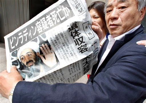 A man shows an extra edition of a Japanese newspaper in Tokyo Monday, May 2, 2011, reporting Osama bin Laden, the glowering mastermind behind the Sept. 11, 2001, terror attacks was killed in an operation led by U.S. forces.