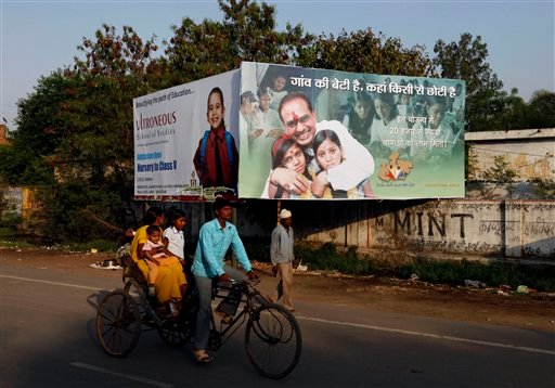 In this photo taken Wednesday, April 13, 2011, a family cycle past a government's advertisement board in support of baby girls in Morena in the Central Indian State of Madhya Pradesh.