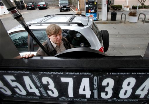 In this March 31, 2011 photo, Jeff Pearson, of Needham, Mass., keeps his eye on the pump while filling his tank with gas at a Gulf station, in Newton, Mass.