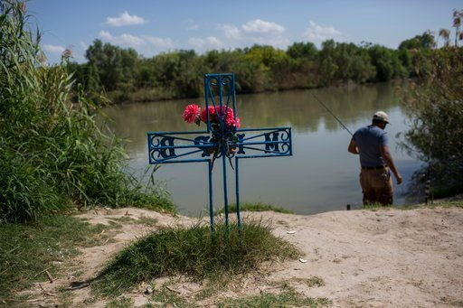 FILE - In this file photo dated Saturday, March 25, 2017, a man fishes in the river near to a cross in memory of a migrant who died trying to cross to the U.S., on the bank of the Rio Grande river in Nuevo Laredo, Tamaulipas state, Mexico, across the bord