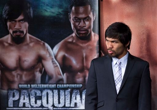Manny Pacquiao, right, arrives at a news conference, Wednesday, May 4, 2011, in Las Vegas. Pacquiao will defend his WBO welterweight title against Shane Mosley on Saturday.